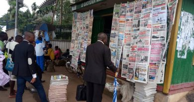Some Cameroonians reading newspaper front pages at a kiosk adjacent the Ministry of Finance in Yaounde