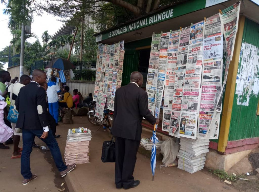 Some Cameroonians read newspaper headlines at a kiosk adjacent the Ministry of Finance in Yaounde.